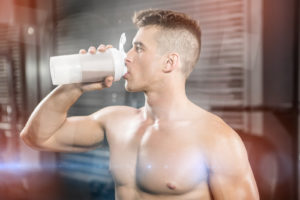 Bodybuilder drinking protein shake at gym